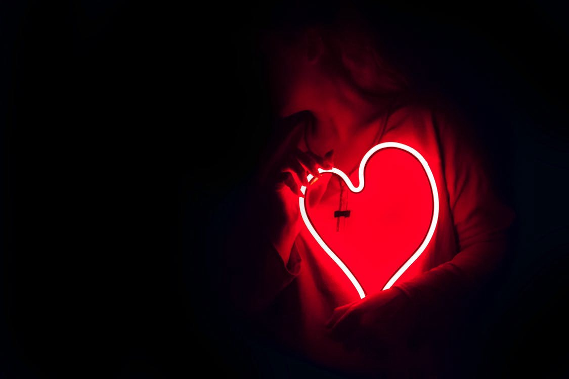 A woman holding a red neon heart in a dark room