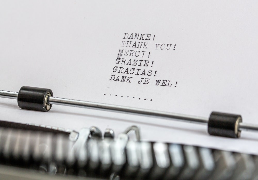 "A close up of a typewriter with the words ""thank you"" written in multiple languages"