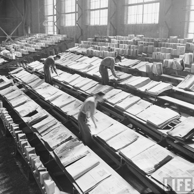 Men drying out state library books damaged by fighting the Lewis Cass State Office Building fire in Michigan, 1951.