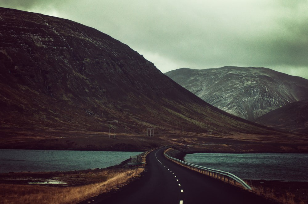 A wide open road with a mountanous background