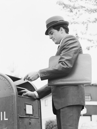 1950's man in a suit posting a letter in an American letter box