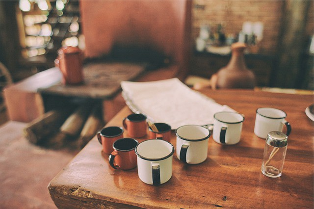 Several empty coffee mugs on a desk where someone has been working.