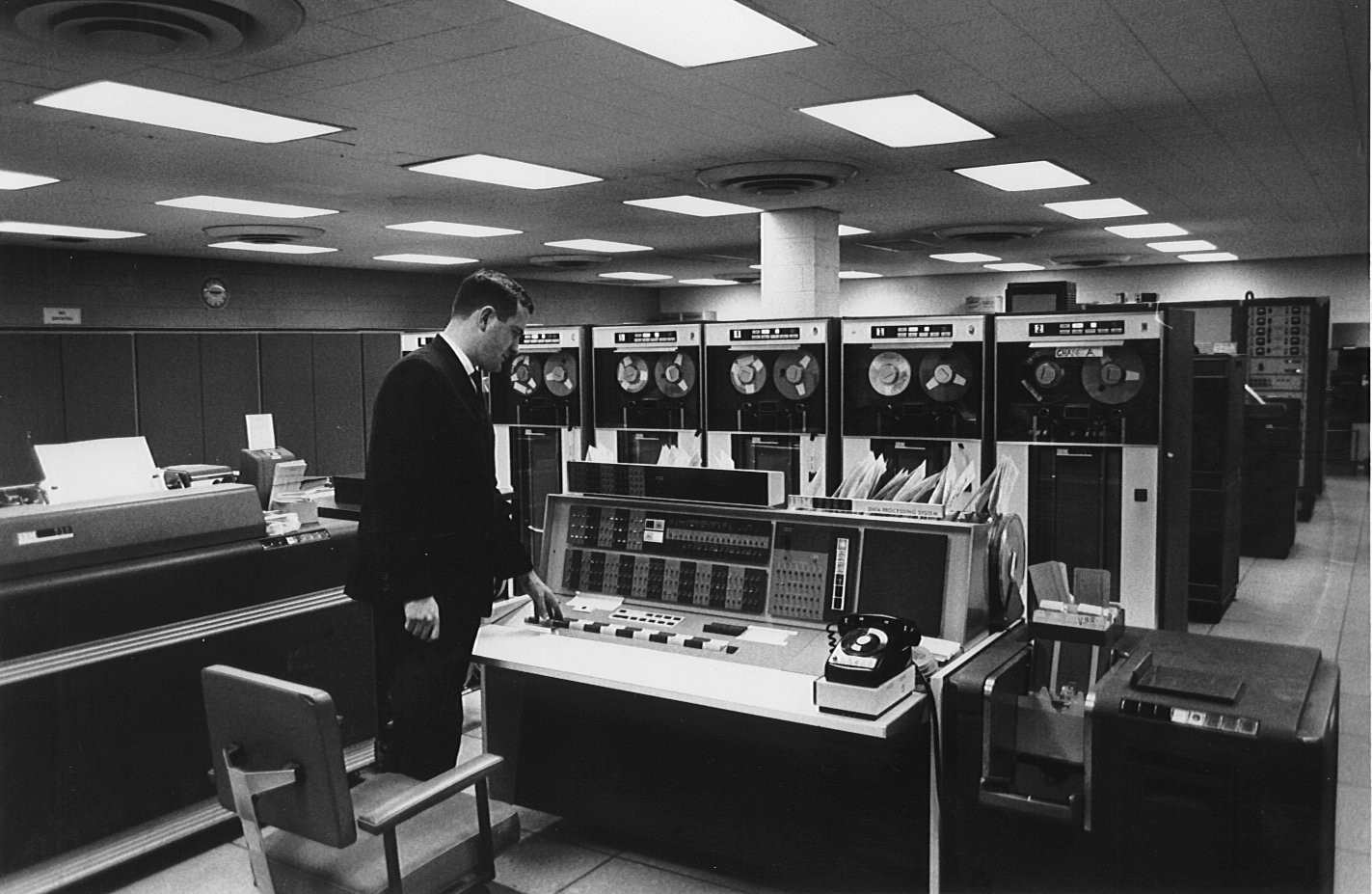An office worker stood next to a very early, and very large computer in the 1970s.