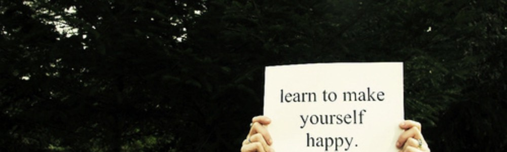"""A person holding the written sheet of paper """"learn to make yourself happy"""""""