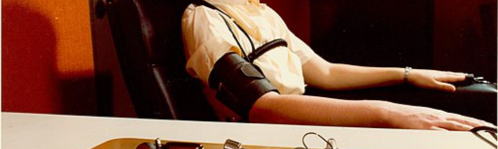 Demonstrating the administration of the polygraph, the polygrapher making notes on the readouts.