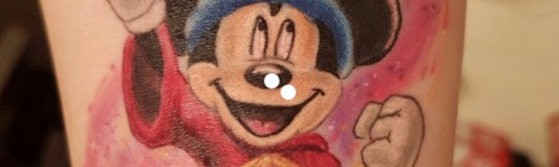 Micky Mouse pointing upwards while wearing wizard hat from the film Fantasia.