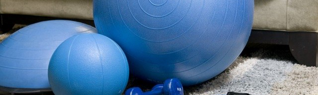 A collection of small blue at home workout equipment on a beige rug with a beige couch in the background.