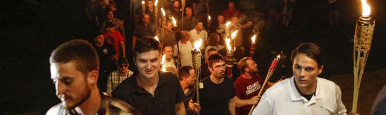 White men carrying tiki torches in a line