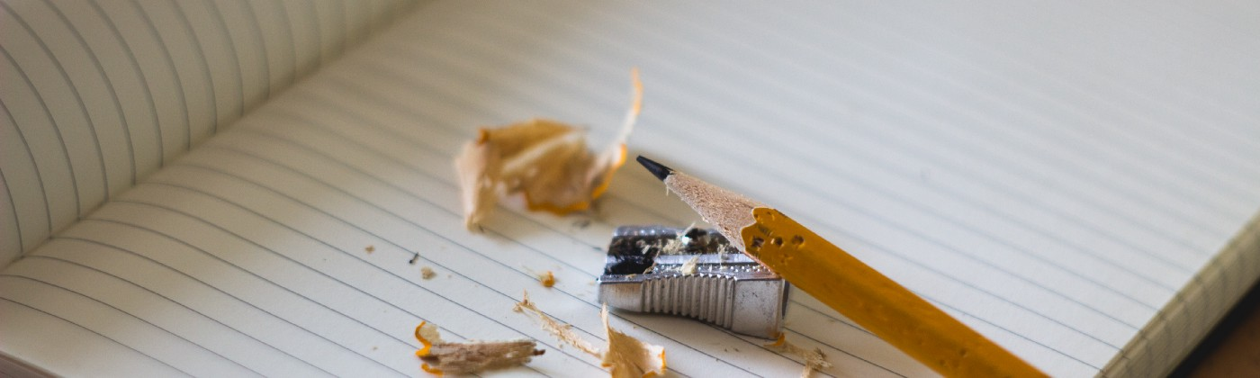 Pencil sharpening over an open notebook.