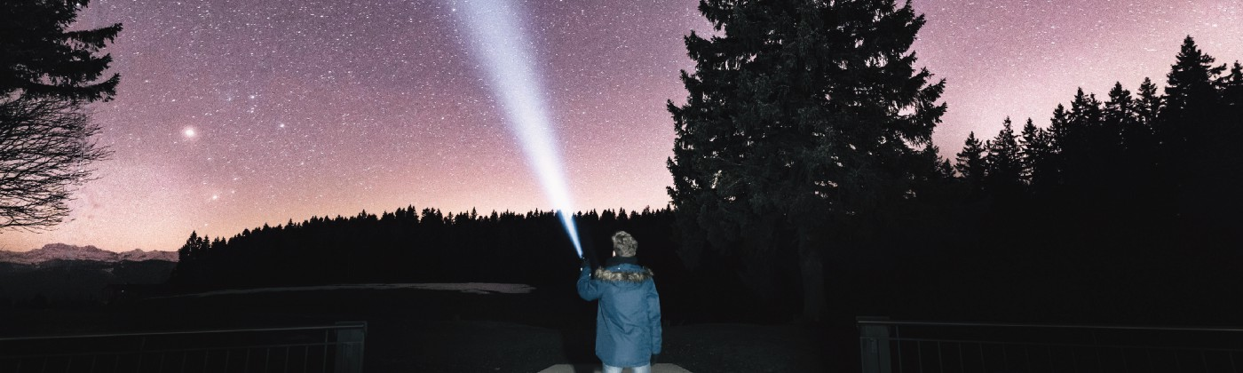 Photo of a man pointing a flashlight up towards a starry sky.