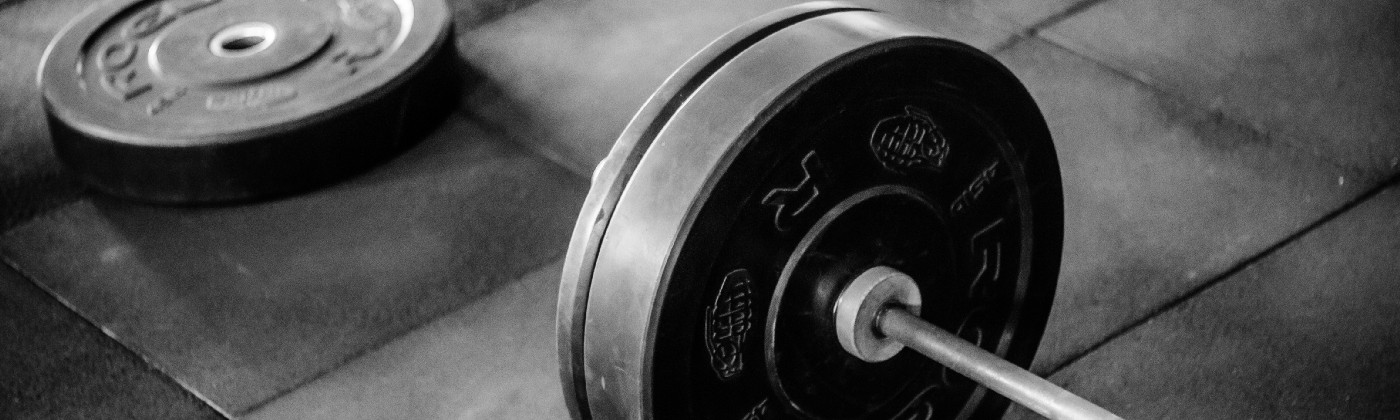 barbell on tiled floor, one plate lying next to barbell