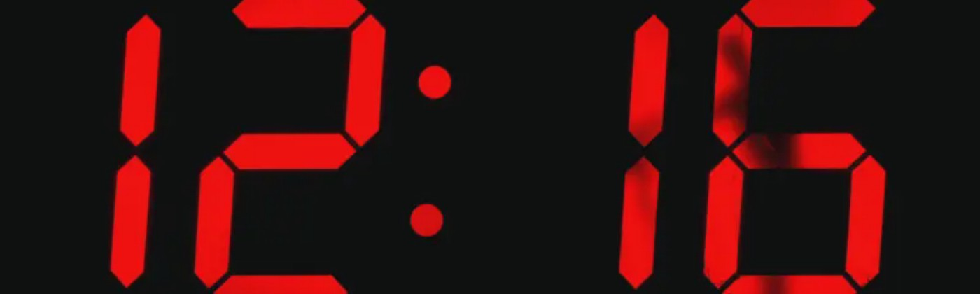 """Marten Baas's """"Digital Analog Clock"""" displaying 12:16 in red numbers, with a faint silhouette of a person peeking through."""