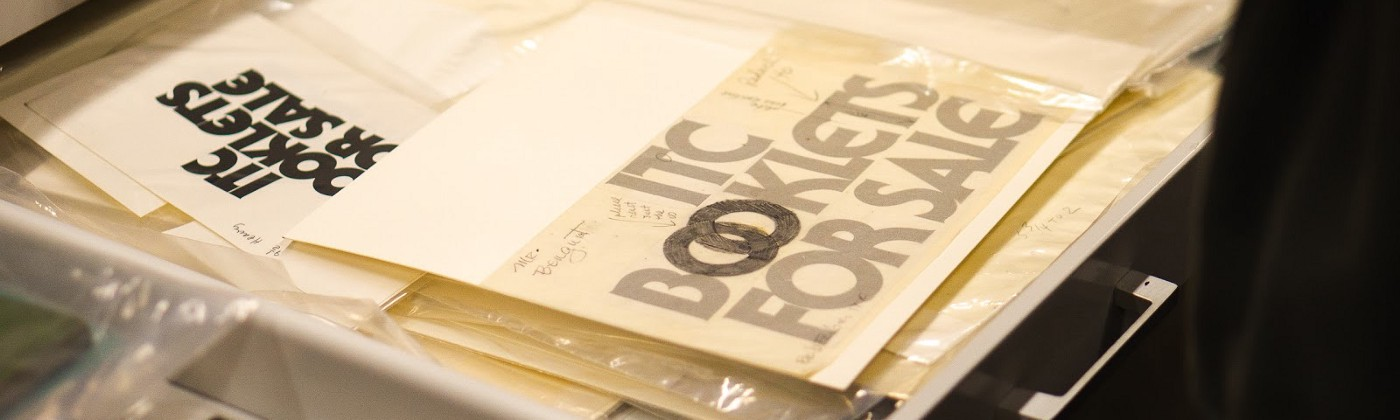 An open drawer containing typographic specimen sheets, with overlaid tracing paper and pencil markings.
