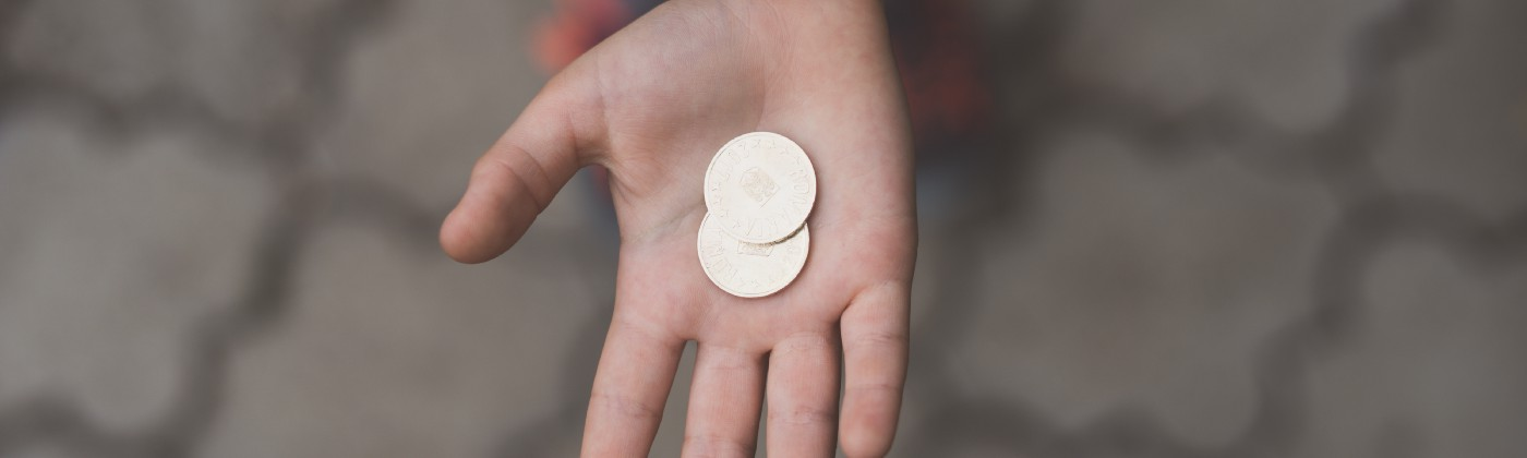 Hand holding two coins in its palm