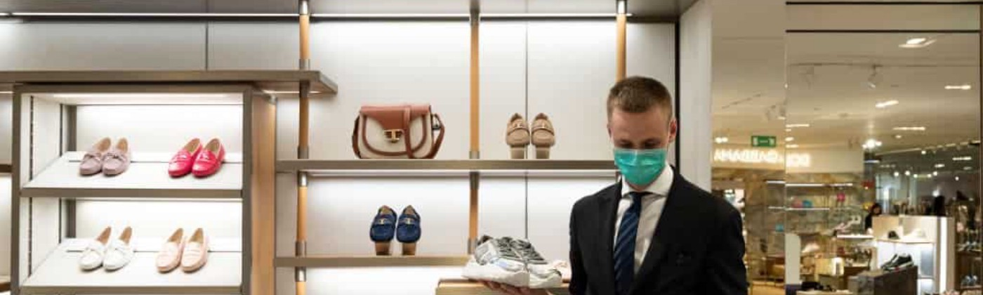Salesperson as Tod's wears a mask at work