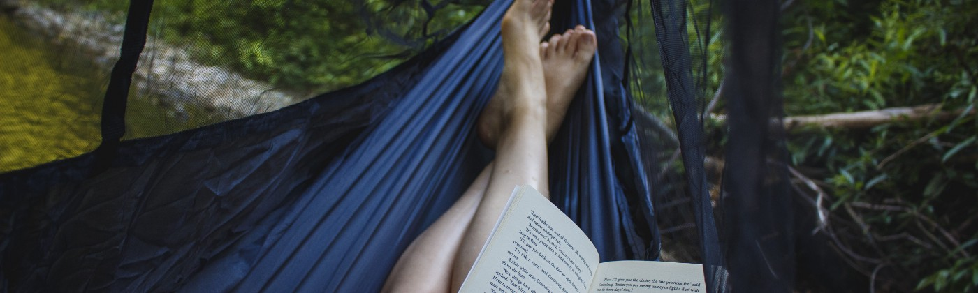 Photo by Katya Austin of legs of a person laying in a hammock in a forest, books in their lap, water bottle by their side.