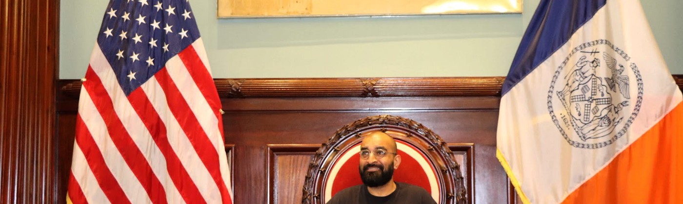 A man with black beard and glasses sits at a large wooden desk between the American flag and New York flag.