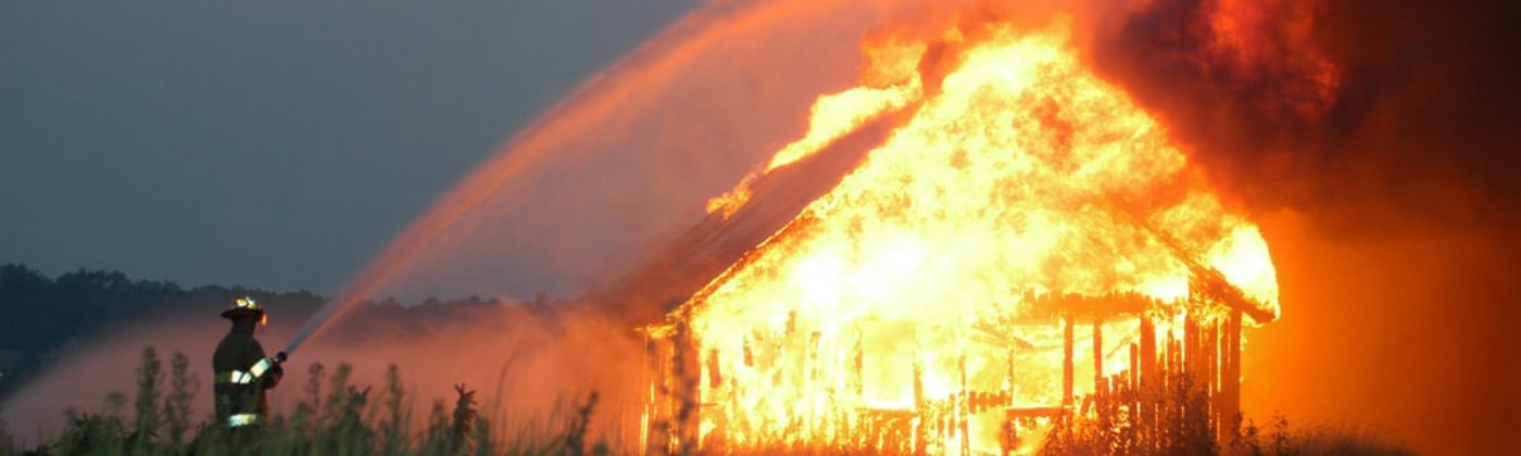 Firefighter aims water hose at burning wood shed in a farm field.