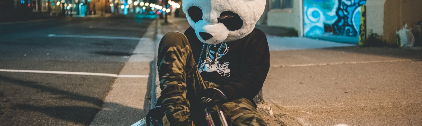Person in a panda head costume sitting on a curb with empty bottles.