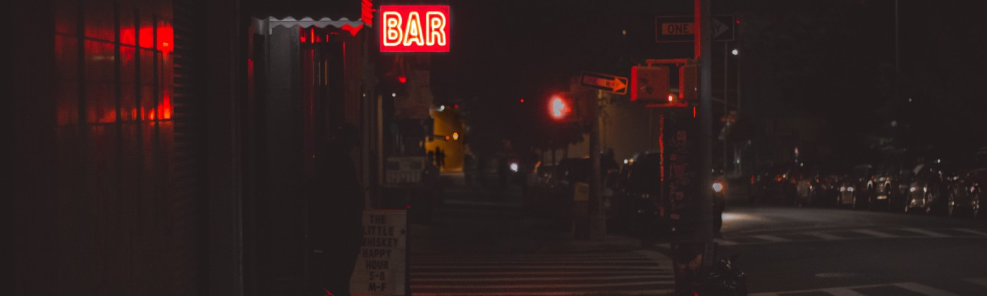 A neon bar sign on a dark city street.