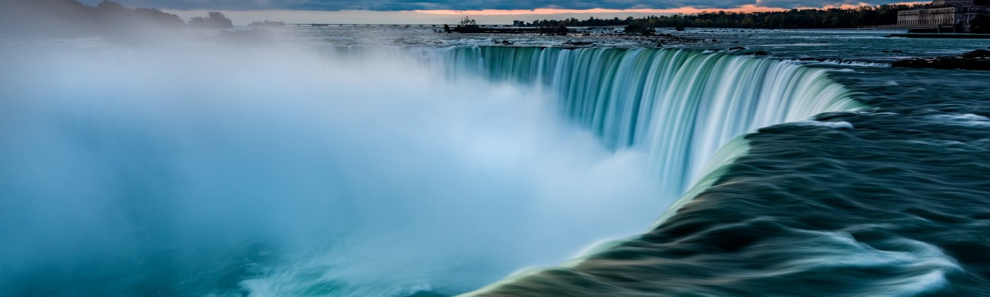 Niagara Falls from a side view. Deep blue water and cloudy skies.