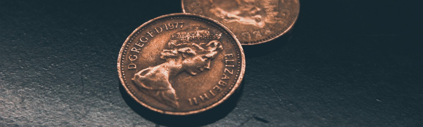 Two pence coins on a scratched black surface