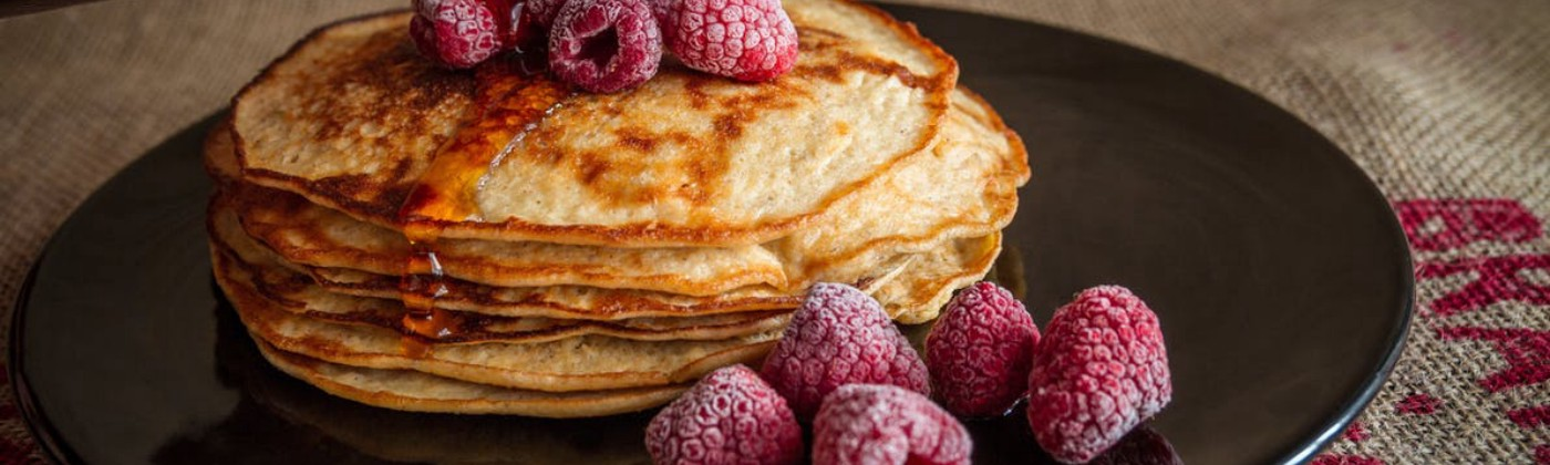 A stack of pancakes and frozen berries on a plate being covered in maple syrup poured from a bottle