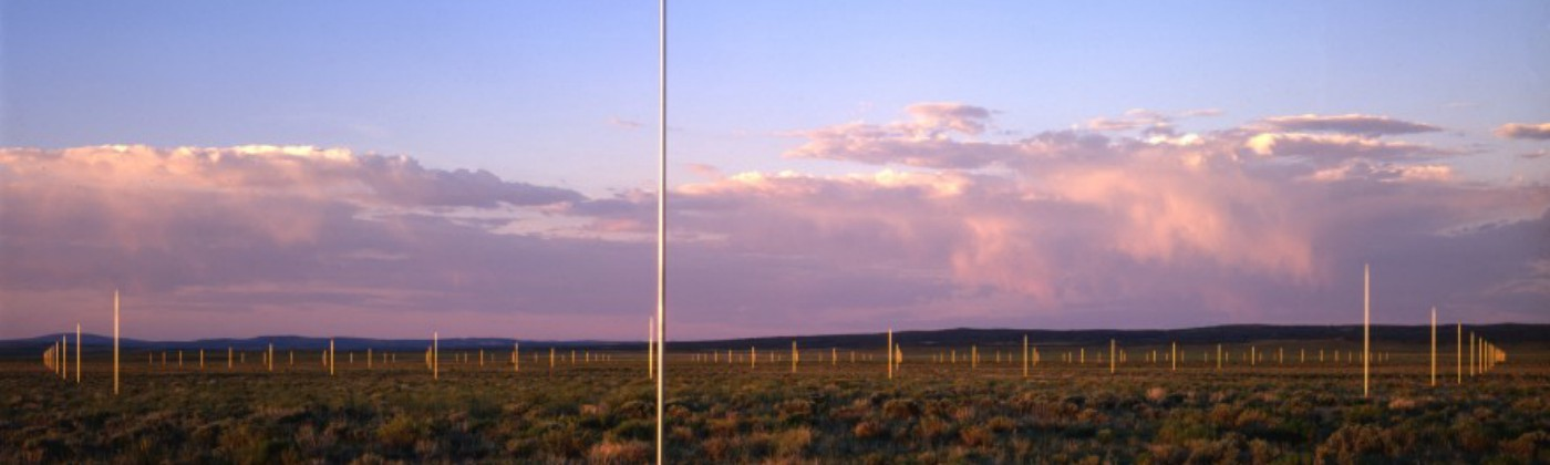View of Lightning Field installation pink clouds and pink light across the land.