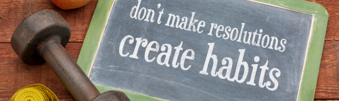"A chalkboard sign for healthy eating habits. ""Don't make resolutions, create habits""."