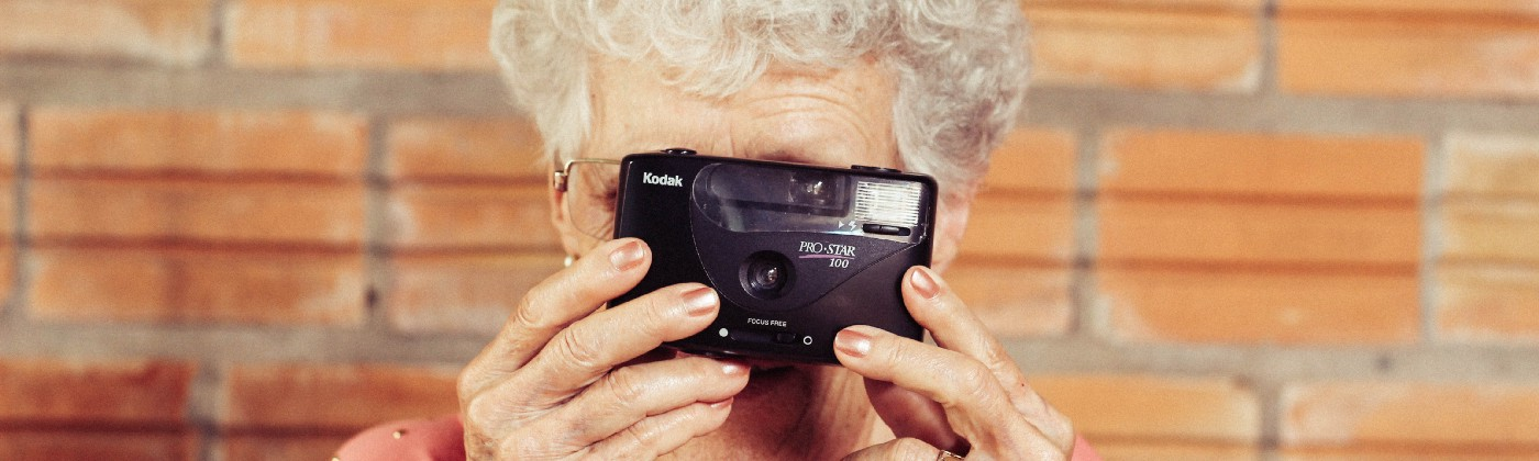 A grandma holding a camera pointing at the screen.