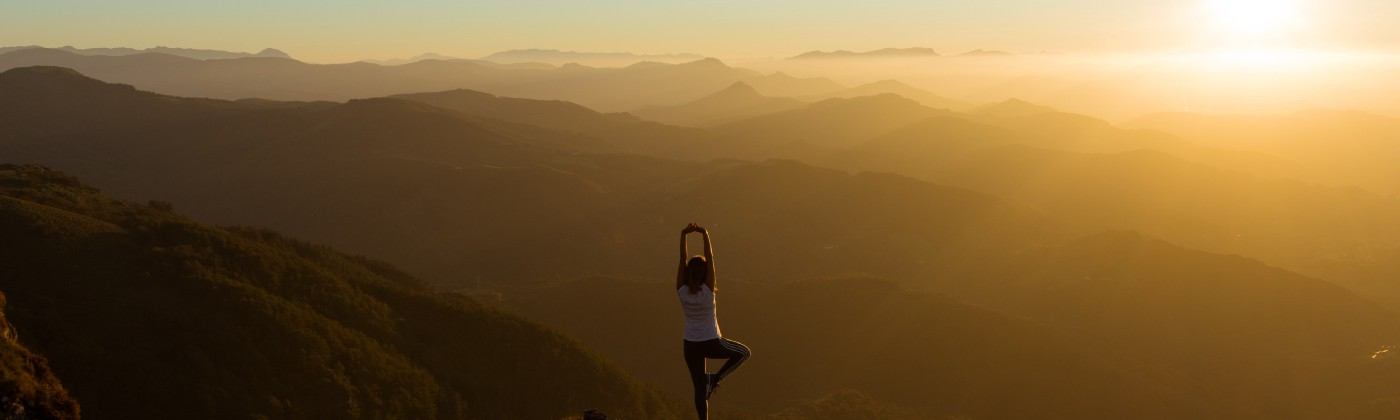 woman doing yoga on the top of a hill