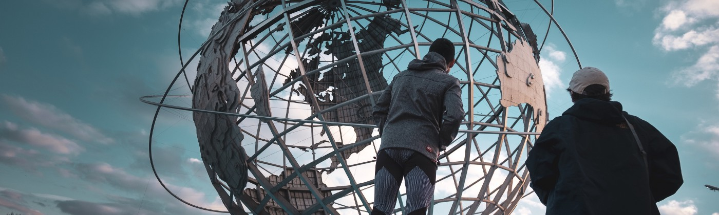 Person standing in front of a large world globe.