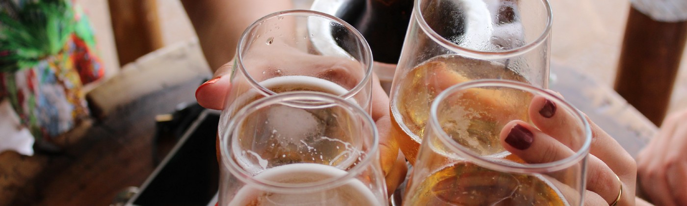 Four people clinking glasses of beer and wine