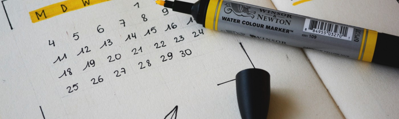 Hand-written calendar with some highlights. An open highlighter sits to the right.