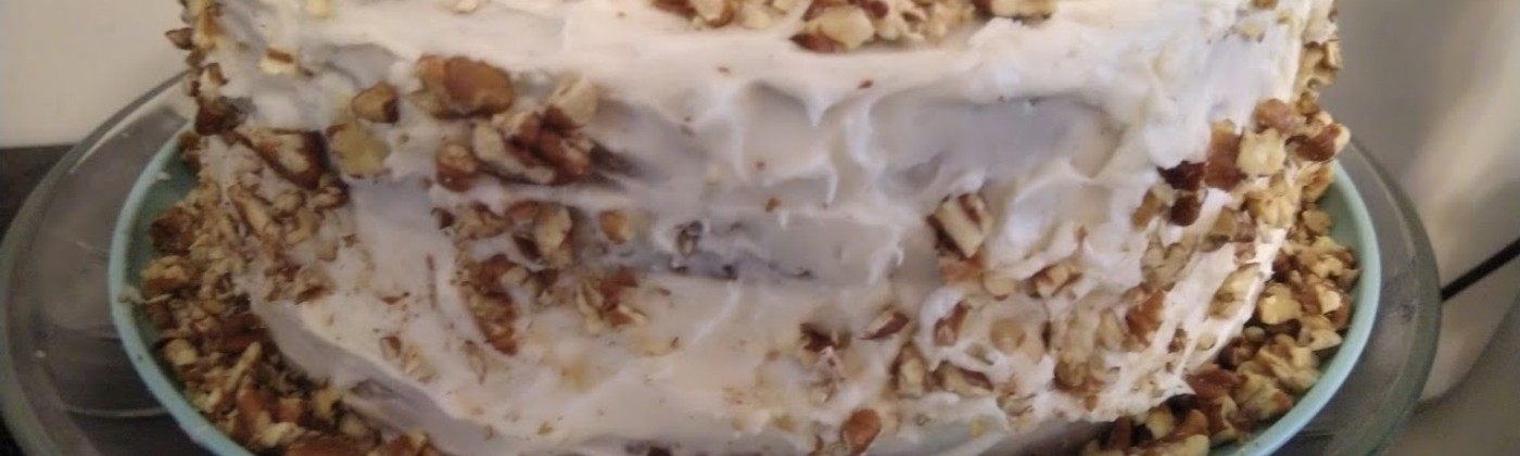 a 3-layered cake with white cream cheese icing, dusted with chopped pecans