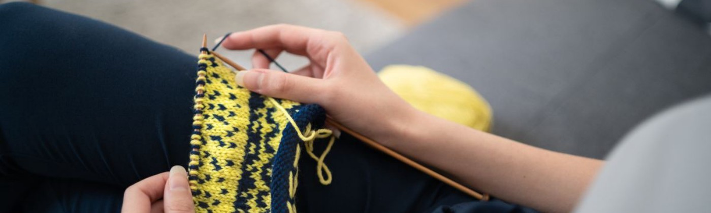 Legs and torso of a person sitting on a couch holding yellow and blue knitting in their hands