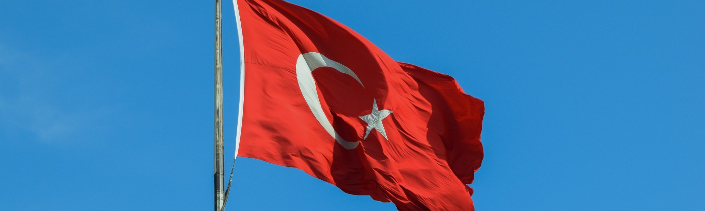 Turkish flag hanging on a flagpole blowing in the wind with a bright blue sky.