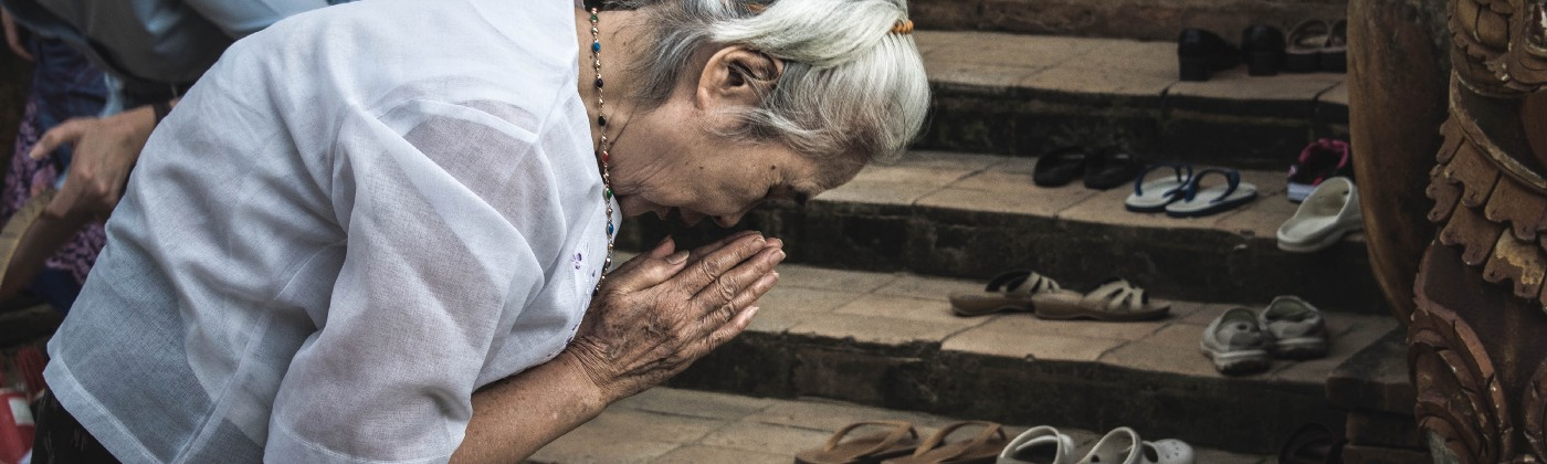An elderly woman bowing with hands clasped in prayer outside a place of worship