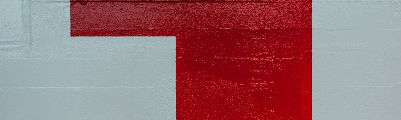 """A big red """"one"""" painted on a white wall with blue shadows"""
