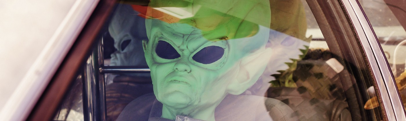 Person in driver seat of a car wearing an alien costume