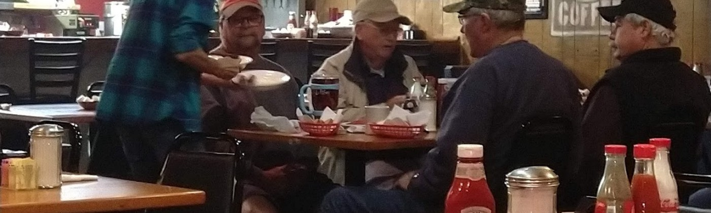 A waitress at a diner serves a group of older men gathered around a table
