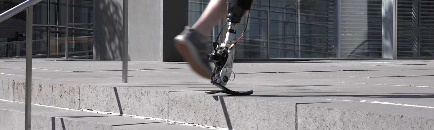 A man with a prosthetic leg climbs stairs