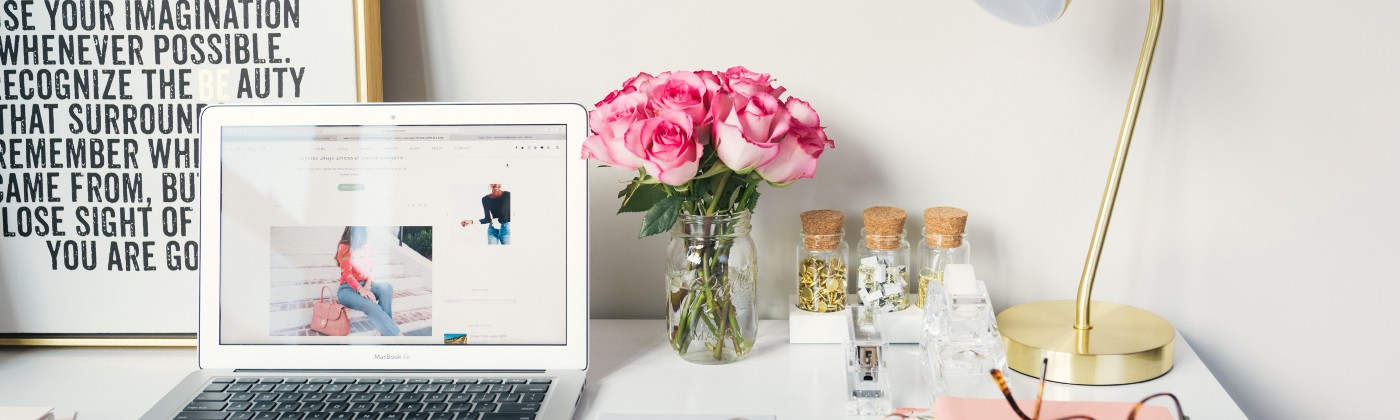 a white desk with pink roses, white laptop, gold lamp, books and glasses