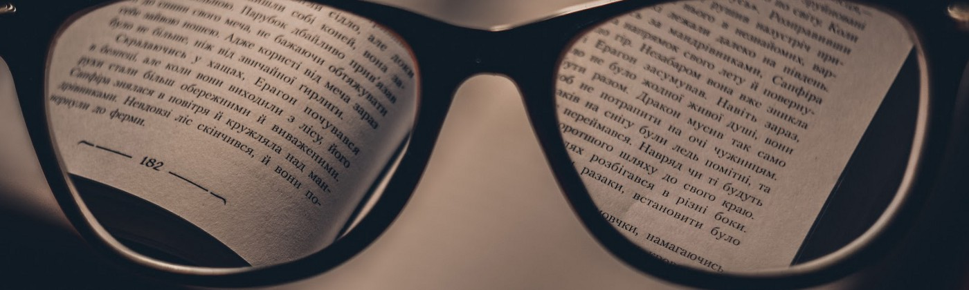 A pair of glasses peering into a book