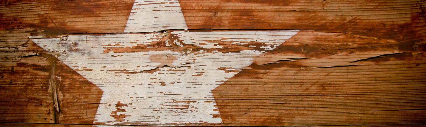 One faded white star on a piece of weathered wood