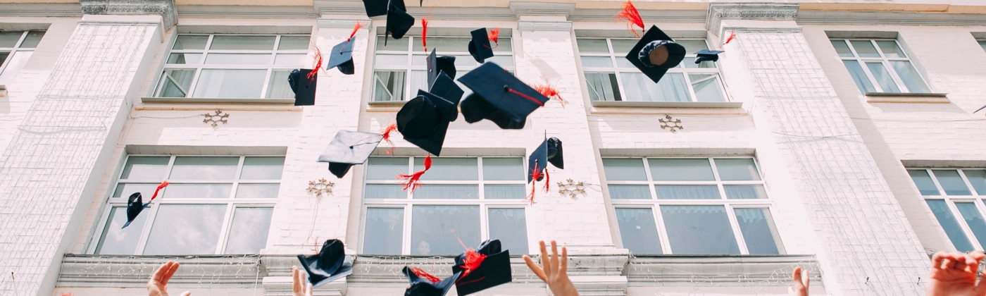 University students on graduation day throwing their caps in the sky
