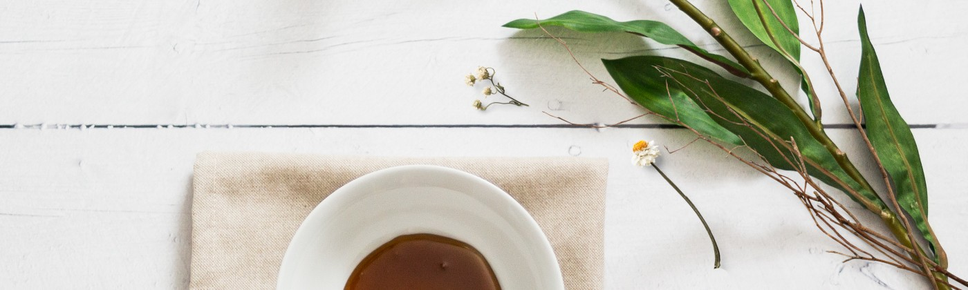 Honey in a bowl next to a white flower.