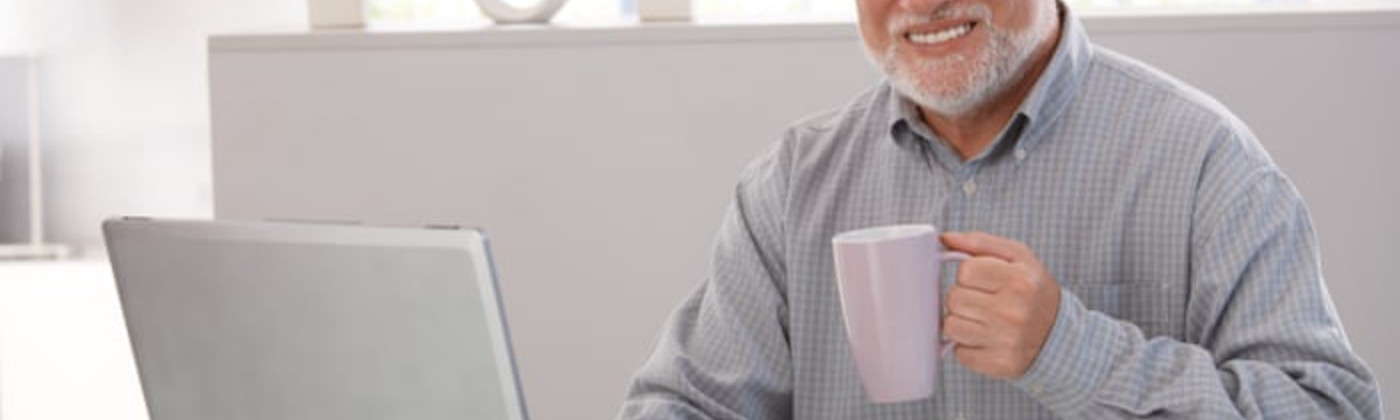 A man works happily from home on a computer.