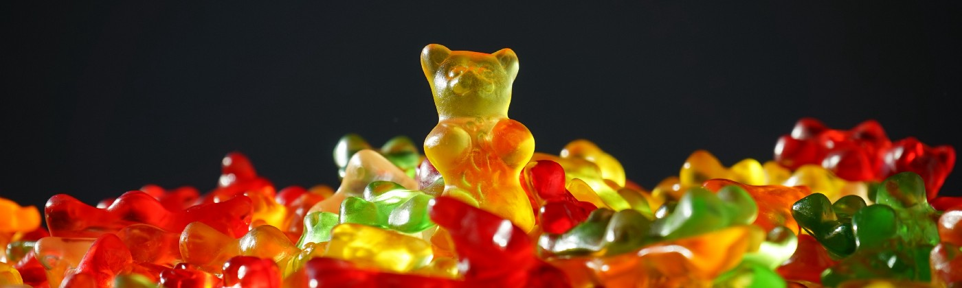 A pile of gummy bears with a tall orange one sticking out on top of it.