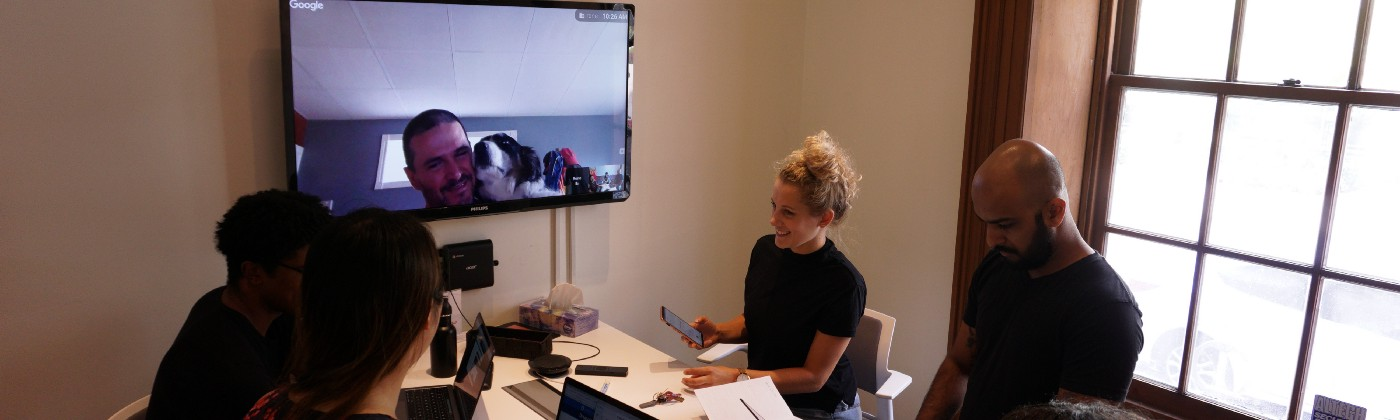 Five people gathered around a table with laptops at a meeting and an additional person appearing remotely on a TV.